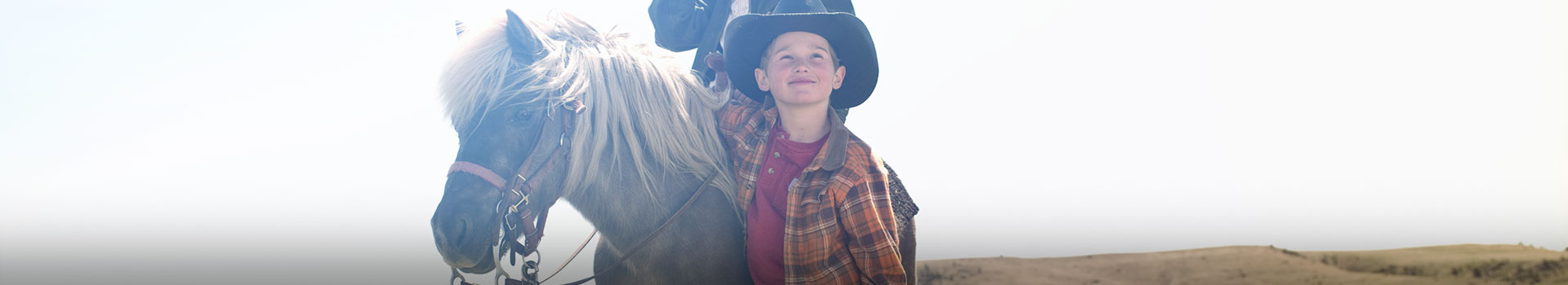 young boy in cowboy hat standing by pony