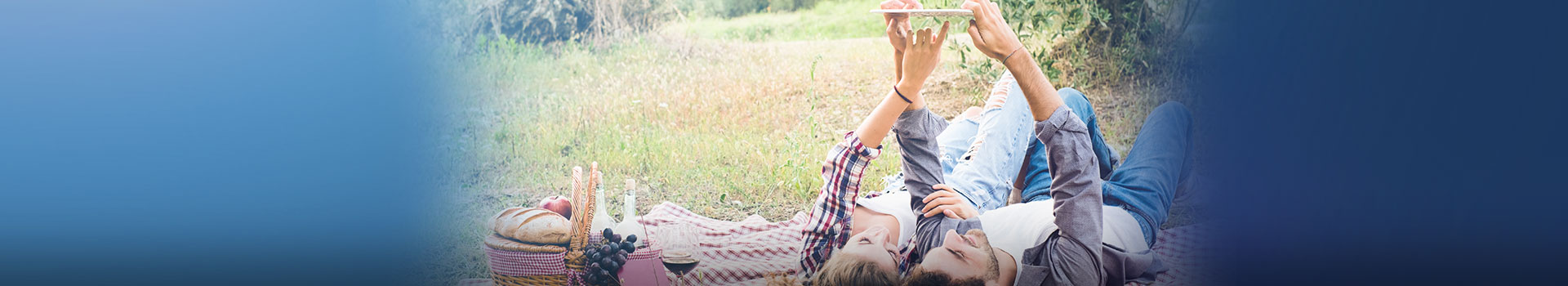 Young couple on picnic blanket looking at something on mobile phone