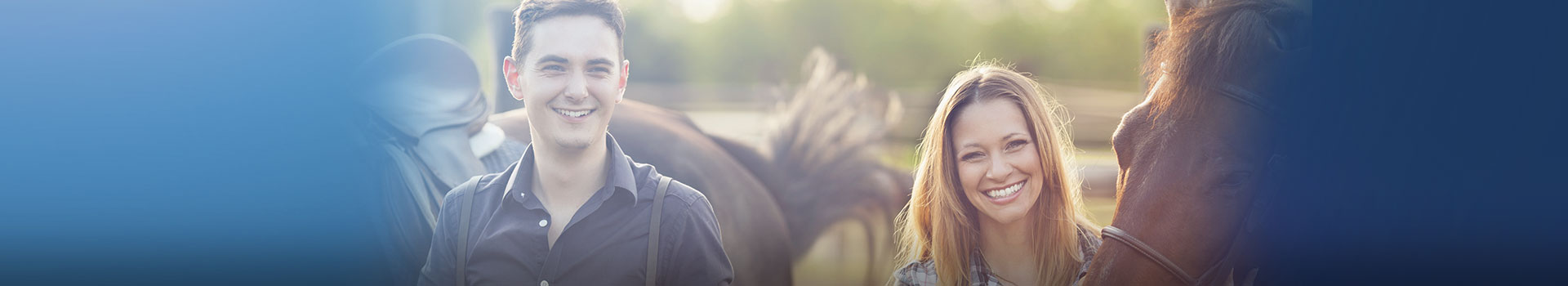 young man and woman standing outside next to horses (1)